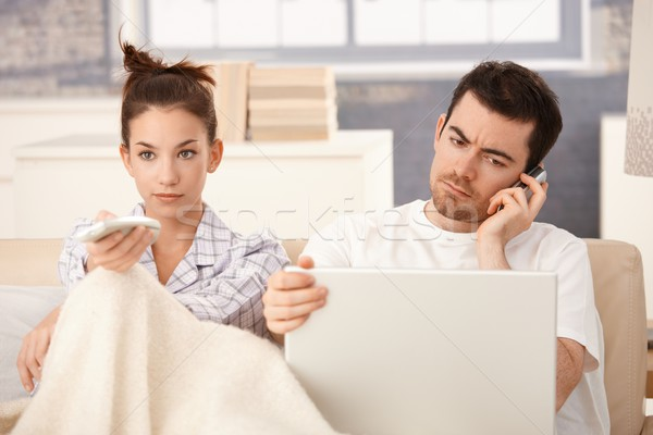 Stock photo: Young couple in bed man working woman watching tv