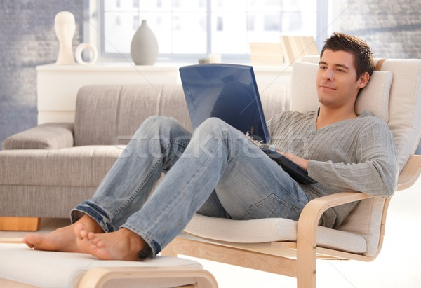 Goodlooking young man relaxing at home with laptop Stock photo © nyul