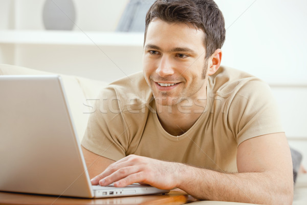 Zdjęcia stock: Człowiek · za · pomocą · laptopa · domu · szczęśliwy · młody · człowiek
