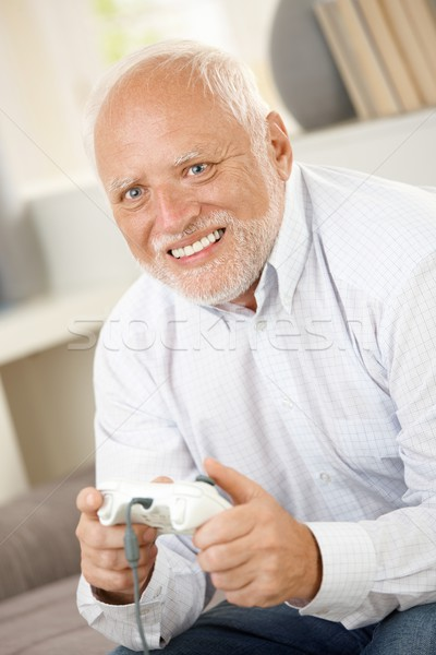 Older man having fun with computer game Stock photo © nyul