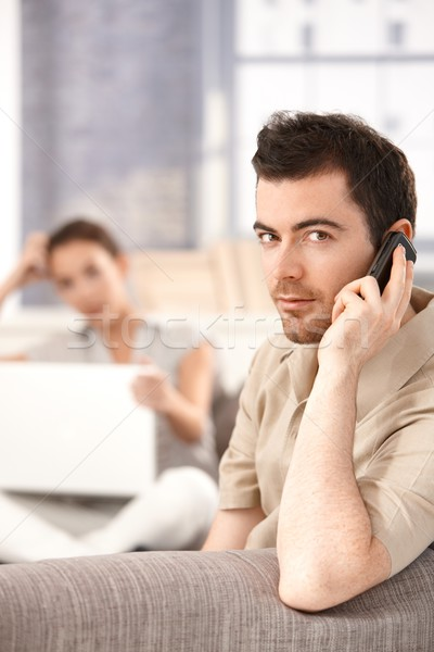 Young male using mobile sitting on sofa Stock photo © nyul