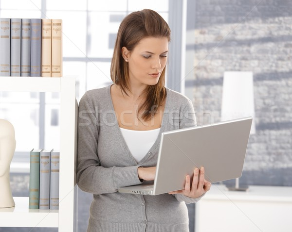 Pretty woman by bookshelf with computer Stock photo © nyul
