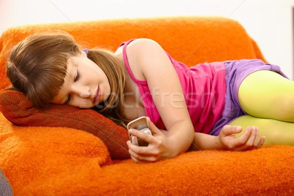 Fiatal lány néz mobiltelefon portré lány mosoly Stock fotó © nyul