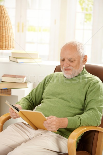 Stock photo: Older man relaxing at home, reading book