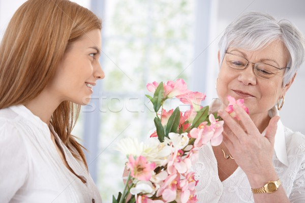 Pretty woman greeting mother with flowers smiling Stock photo © nyul