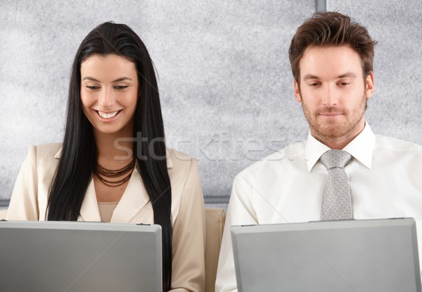 Young colleagues working on laptop smiling Stock photo © nyul