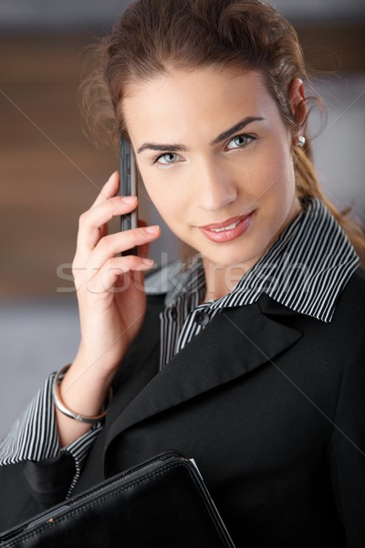 Young businesswoman smiling happily with mobile Stock photo © nyul