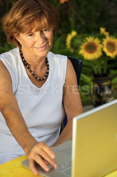 Kıdemli kadın dizüstü bilgisayar modern kadın oturma Stok fotoğraf © nyul