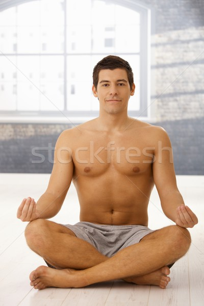 Stock photo: Smiling young man meditating