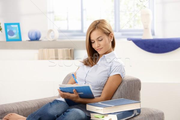 Attractive student doing homework in living room Stock photo © nyul