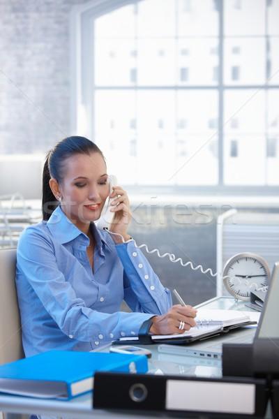 Cheerful businesswoman on landline call Stock photo © nyul