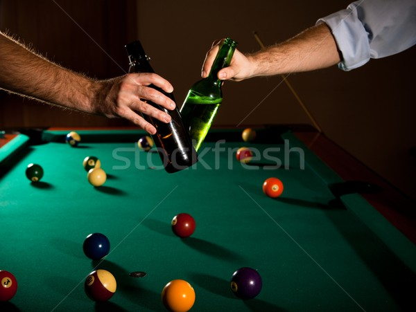Stock photo: Clinking beer bottles at snooker