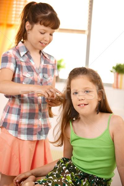 Cute girl combing friend's hair Stock photo © nyul