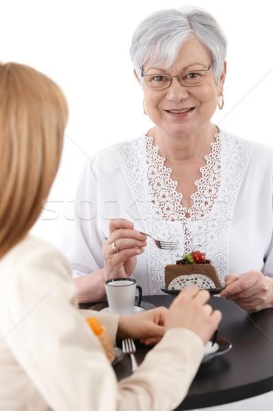 Portrait of mature lady eating cake smiling Stock photo © nyul