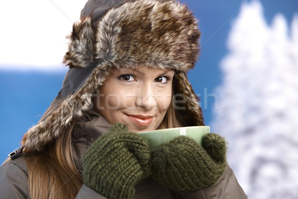 Young female dressed up warm drinking tea smiling Stock photo © nyul