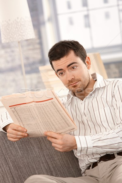 Young male reading bad news from newspaper Stock photo © nyul