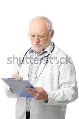 Senior doctor looking at clipboard Stock photo © nyul
