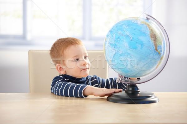 Sweet ginger-haired little boy studying globe Stock photo © nyul