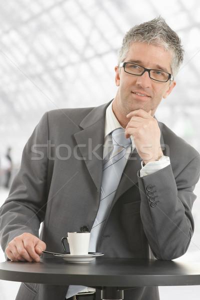 Empresário pensando café em pé mesa de café escritório Foto stock © nyul