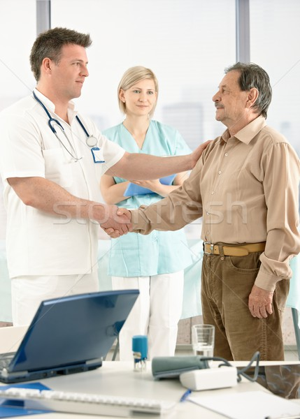 Doctor congratulating senior patient on recovery Stock photo © nyul