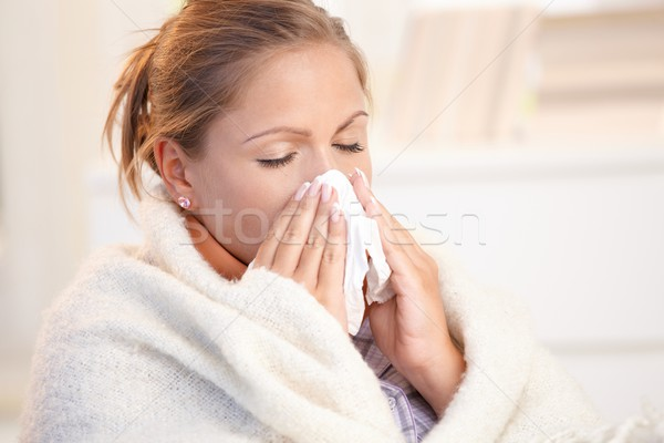 Young woman having flu blowing her nose Stock photo © nyul