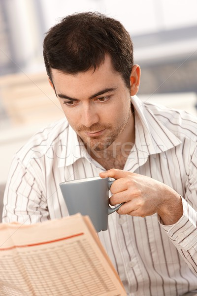Stock photo: Young man reading news drinking tea in the morning