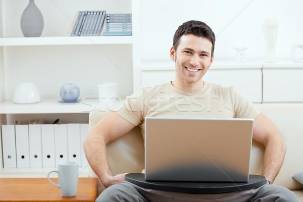 Stok fotoğraf: Adam · dizüstü · bilgisayar · kullanıyorsanız · ev · mutlu · bej