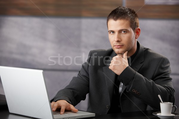 Goodlooking manager sitting at desk in office Stock photo © nyul