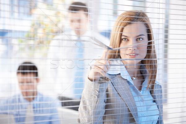 Nosy businesswoman peeping through blind smiling Stock photo © nyul