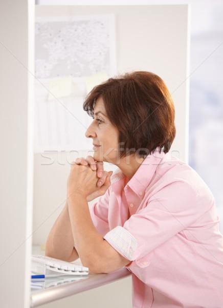 Senior donna seduta ufficio pensare sorridere Foto d'archivio © nyul