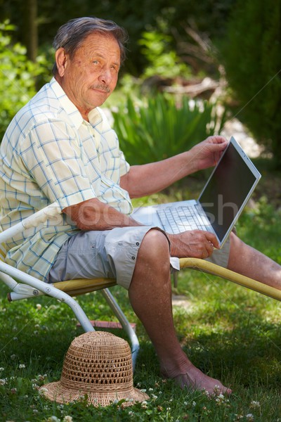 Senior man using computer outdoor Stock photo © nyul