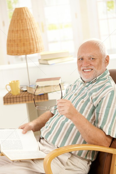 Stock photo: Happy pensioner reading at home