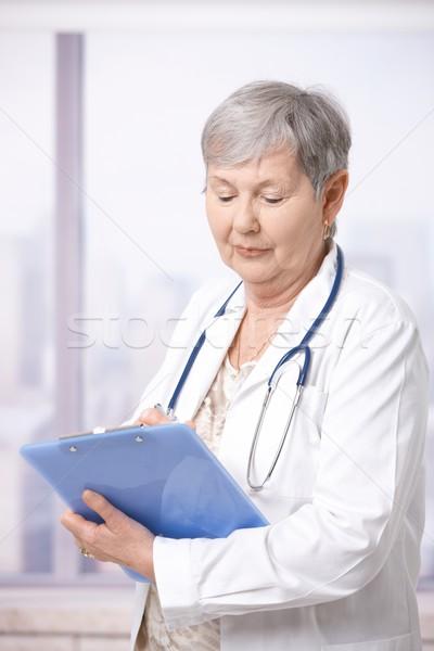 Stock photo: Senior doctor taking notes
