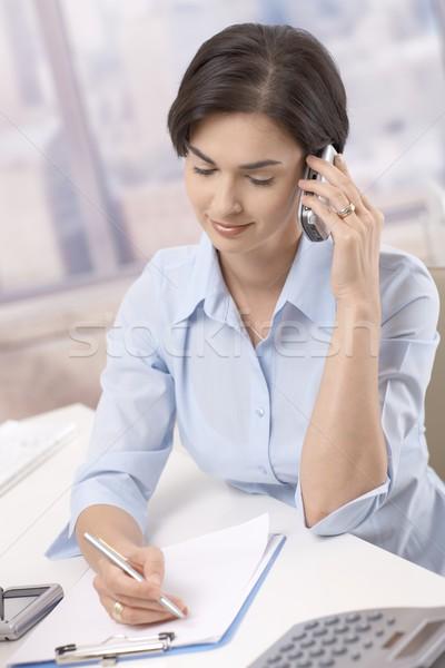 Stock fotó: üzletasszony · mobiltelefon · iroda · portré · mosolyog · jegyzetel