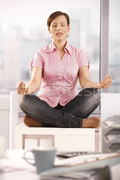 Young businesswoman meditating in office Stock photo © nyul