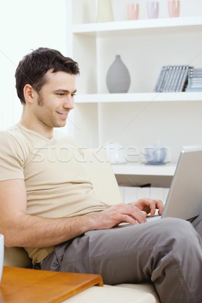 Boldog férfi számítógéphasználat fiatalember póló ül Stock fotó © nyul