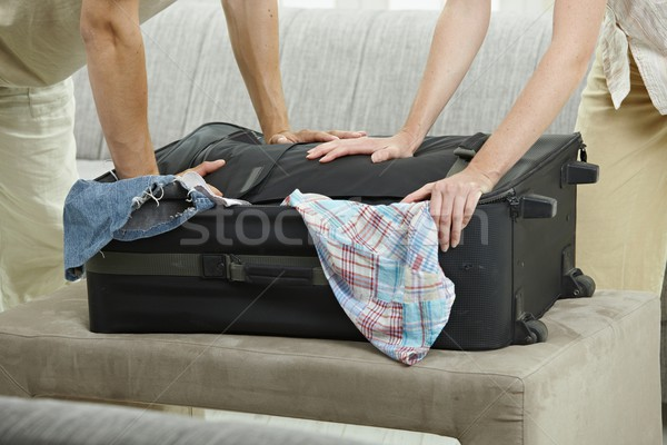 Hands pressing suitcase Stock photo © nyul
