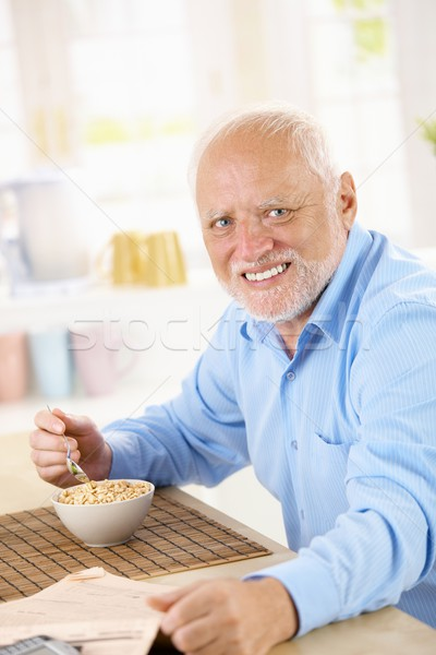 Stock photo: Portrait of older man eating cereal