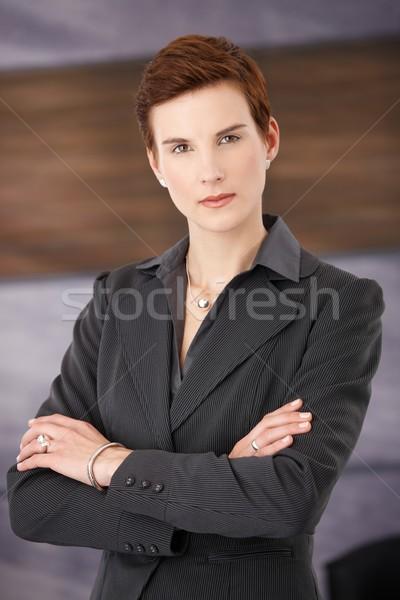 Trendi határozott üzletasszony áll iroda karok Stock fotó © nyul