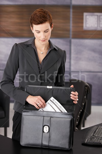 Businesswoman pulling contract from briefcase Stock photo © nyul