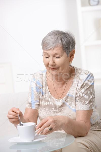 Senior mulher potável café sessão mesa de café Foto stock © nyul