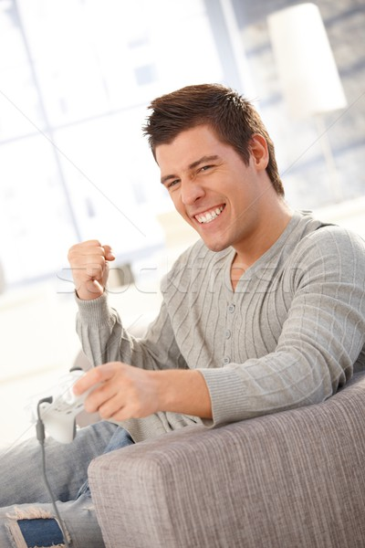 Młody człowiek szczęśliwy gra komputerowa zwycięski domu pięść Zdjęcia stock © nyul