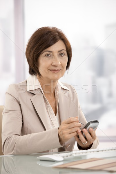 Portret vrouwelijke zakenvrouw smartphone glimlachend Stockfoto © nyul
