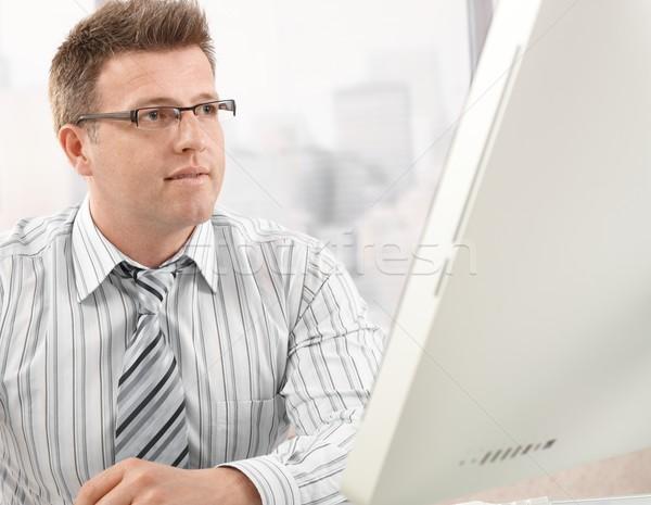 Mid-adult businessman looking at computer screen Stock photo © nyul