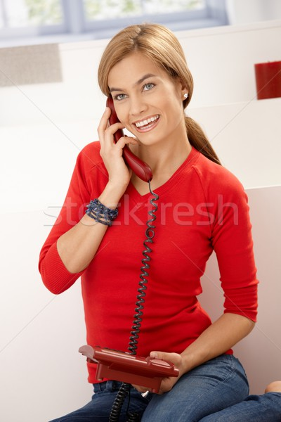 Happy woman in red talking on phone at home Stock photo © nyul