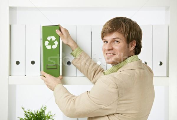 Businessman removing green folder from shelf Stock photo © nyul