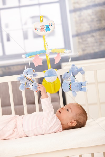 Baby playing with bed mobile Stock photo © nyul