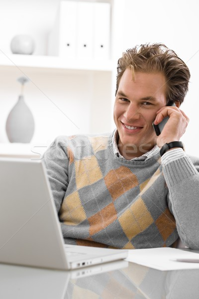 Fiatalember otthoni munka laptopot használ hív telefon otthon Stock fotó © nyul