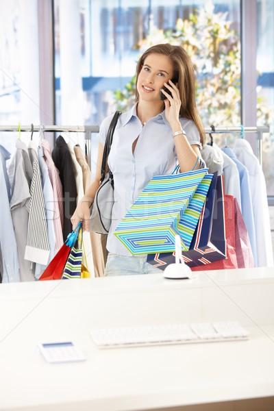 ストックフォト: 女性の携帯電話 · 服 · ショップ · 女性 · 立って