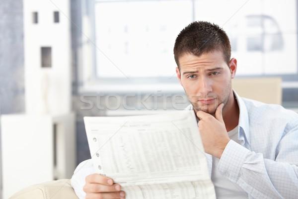 Fiatalember olvas rossz újság otthon néz Stock fotó © nyul
